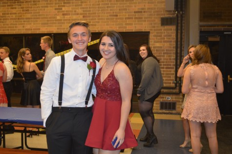 Emily Lenaghan (and Jack Billek) dressed in a burgundy low cut dress with a ruffled bodice.