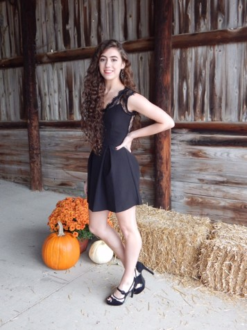 Isabelle Urben dressed in a black v-neck dress with a lace overlay on the sleeves and back.